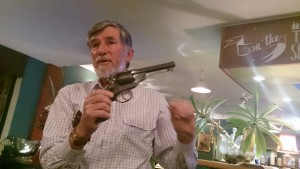 Peter Smith holding a gun owned by a member of the Clarke Gang