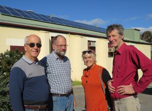 Mike Young, John, Angie and Frank discuss planning for the expo. School of Arts Hall with solar cells purchased by Rotary in the background.